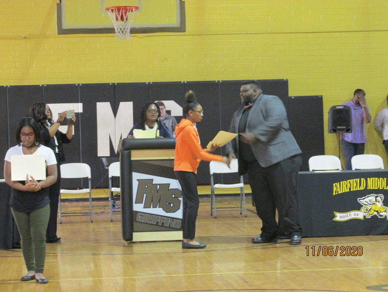 Mr. Brunson handing out Honor Roll Certificate