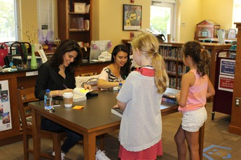Authors Roshani Chokshi and J.C. Cervantes signing their books at F.AVE