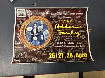 The cast signs the musical poster