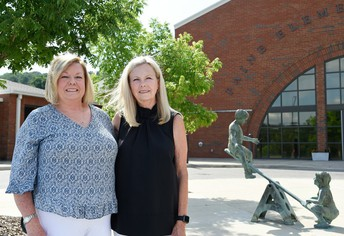 two women standing in front of Paine Elementary School