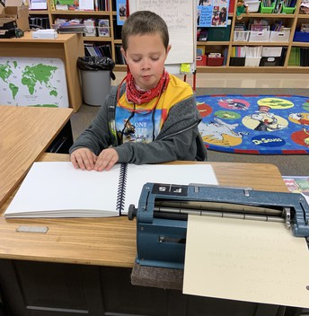 Billy sitting at his desk reading a braille book; his brailler with paper in it sits beyond his book
