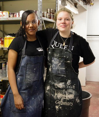 Two dean female carpentry students posing for a photo with their work aprons on.