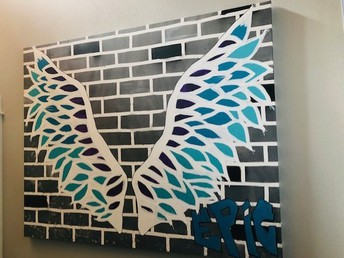blue & white painting of wings on brick wall background with the word Epic on corner