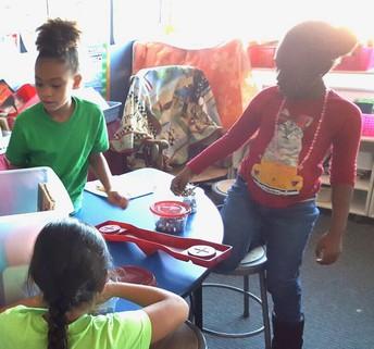 Estudiantes de 2º Grado que Usan Básculas para Pesar Objetos
