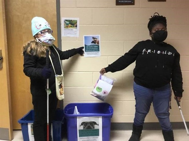 2 students placing a ziplocked bag into a donation bin; one student points to a donation flyer on the wall
