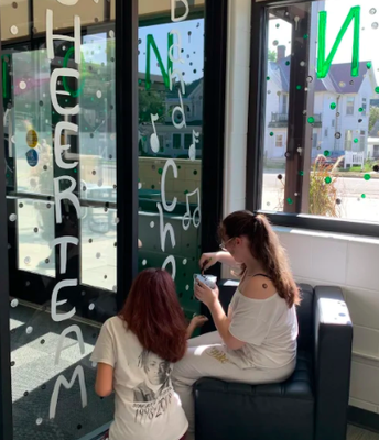 Brooke and Jocelyn painting windows for Homecoming.