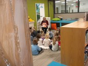 Mrs. Zeppos, 4K aide, with her cherubs in our reading nook,