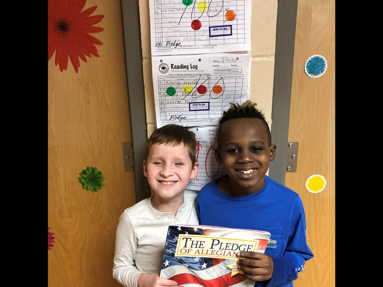 2 male students smiling. Standing in front of a 100 book challenge chart, holding a book titled The Pledge of Allegiance
