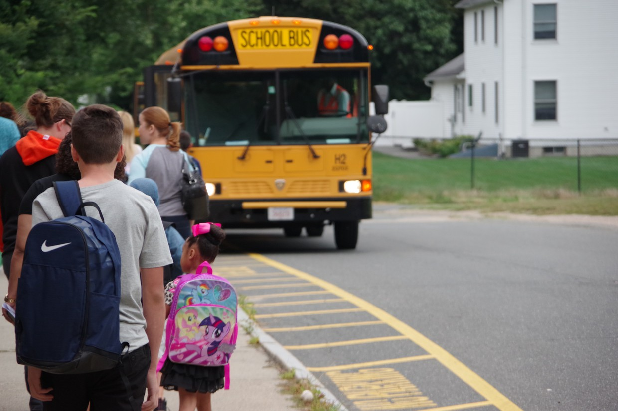 elementary school students line up for the bus