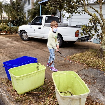 Arabella navigating through a neighborhood; there are 3 garbage bins on the ground to her right and a pickup truck to her left
