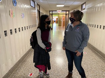 Mrs. Zaza talking about the third quarter with a student.