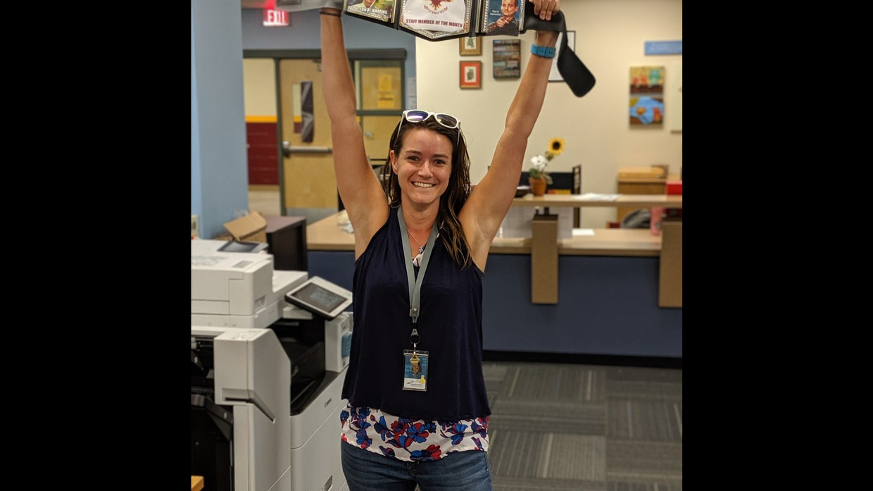 Ms. Huff hoisting the Staff Member of the Month Title Belt