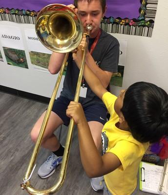 Brenten demonstrates the slide trombone for the children in music.