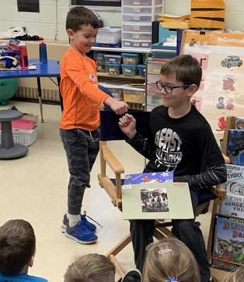 """Brothers (and fellow Munson Elem. students) Noah Vancura (l) and Royce Vancura (r) fist bump and smile after big brother Royce reads """"Knuffle Bunny"""" to Noah and his classmates."""