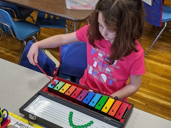 Park Elementary Kindergarten student practices playing the xylophone.