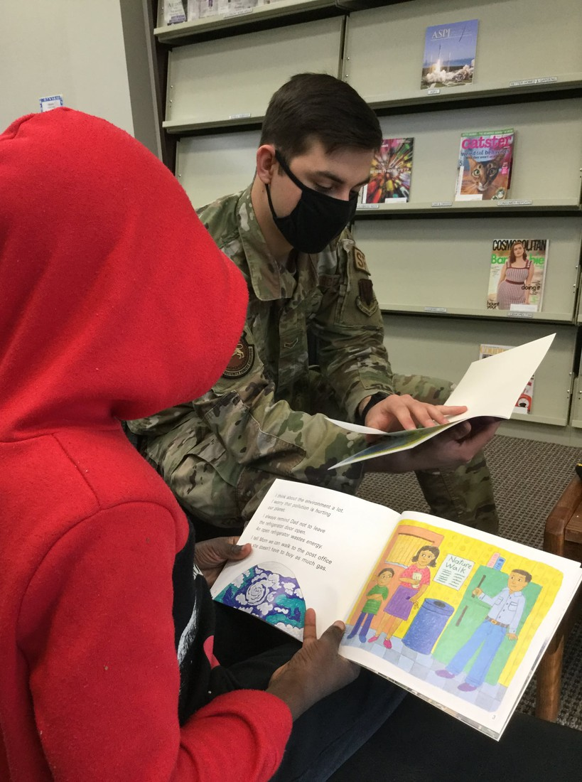 Airman reading with student at CHE