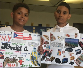 """Two male students showing their """"My Culture and Me"""" posters created in their Kelly School class."""