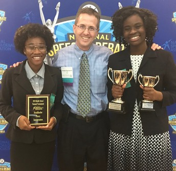 Speech and Debate students and teacher with trophies and plaque