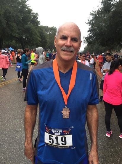Randall Crosby at the conclusion of the Turkey Trot race. He has blue running outfit, a medal around his neck, and bib 519
