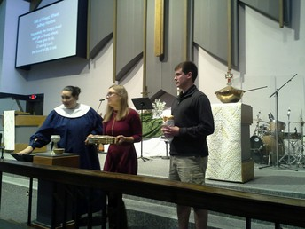 UNT senior Will Atwood (far right) serves communion at First Lewisville United Methodist Church.