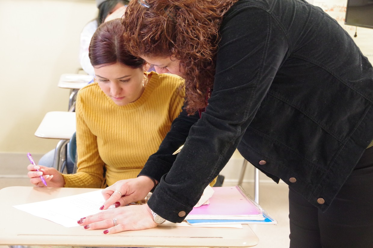 High school female student and staff member working together, reading an assignment.