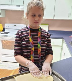 Lacey using hands to manipulate dough