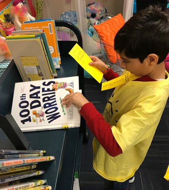 Student placing kindness bookmarks in books