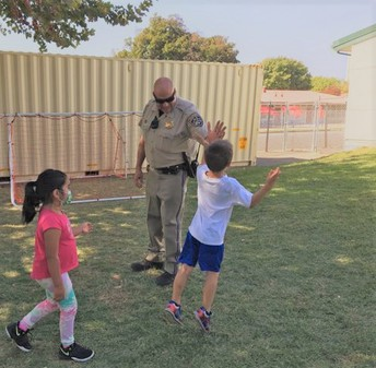 Officer Muzzy Giving Students a High-Five