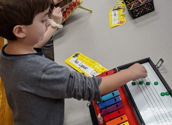 Park Elementary Kindergarten student practices arranging magnetic notes on a musical staff.