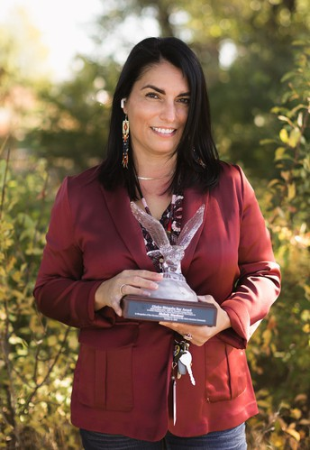 woman in red blazer holding eagle shaped award