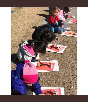 Kinder using art and sun for shadow experiment!