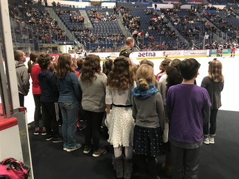 "John Lyman 3rd and 4th graders led by Mr. Meurs prepare to sing ""God Bless America"" at a Hartford Wolfpack game"