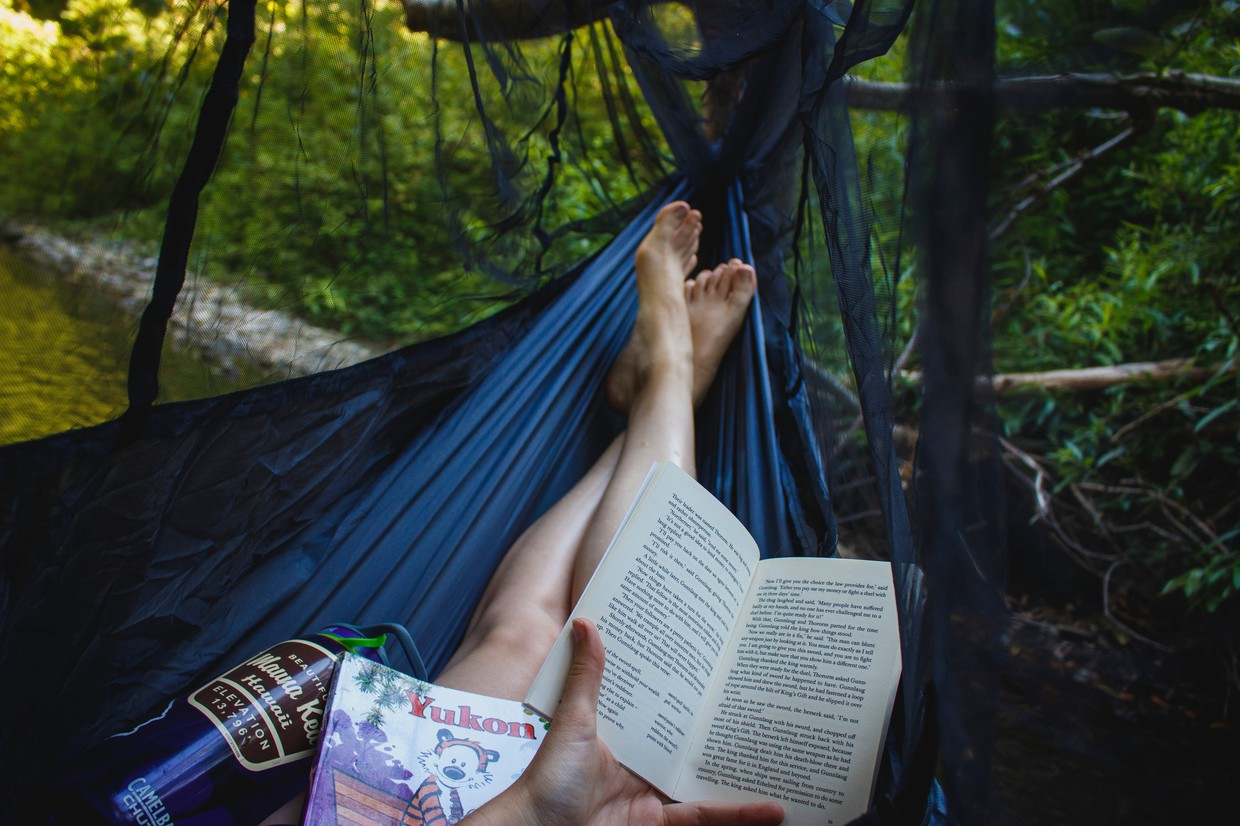 Credit: Unsplash. Summer reading in a hammock with a variety of books.