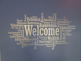 picture of the welcome sign of welcome in multiple languages in the front entrance of the middle school