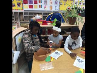 4th grade scholars making turkey hats with preschool scholars!