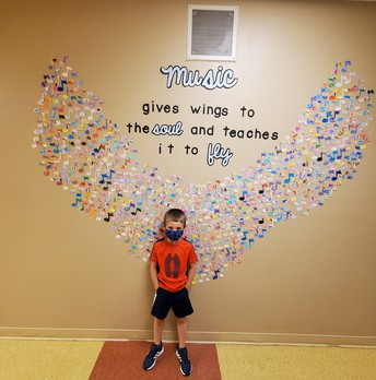 boy standing in front of angel wing created from paper music notes