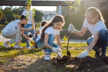 children planting trees in community