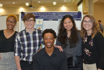 Photo from Jenn Zettler - Five students in business casual clothing stand in front of a research poster. Two of them are Black, one is a person of asian descent, and three are women. All are smiling!