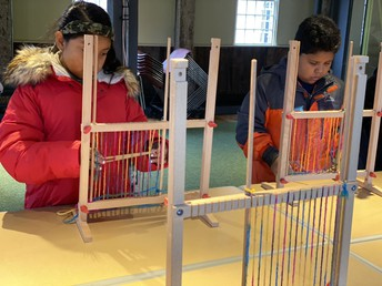 Mrs. DeCiccio's students practice weaving.