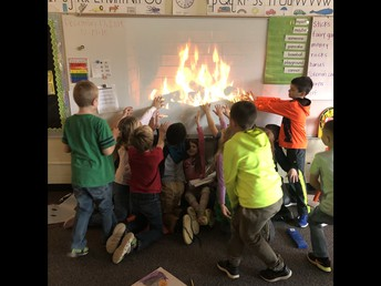 Warming our real hands in front of a pretend fire.