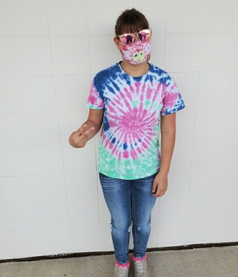 Teagan wearing her tie-dyed shirt of navy, pink, and mint green colors