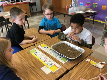 Student experimenting with erosion by blowing soil with a straw.