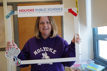 Female HHS teacher holding up a photo booth frame