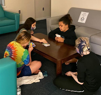 4 students are sitting around a table playing Uno with brailled cards