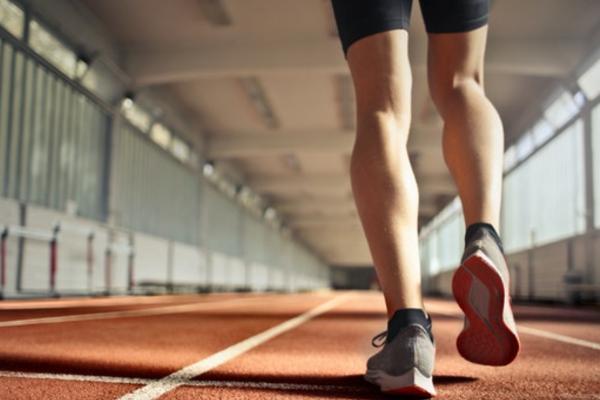 Legs of runner on indoor track