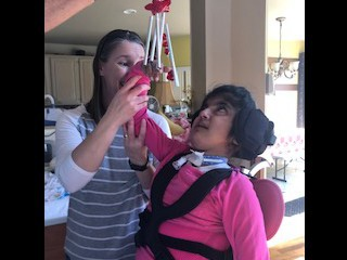 student looks at red chimes held to in her right upper visual field.  Teacher provides support at at elbow and forearm