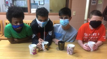 4 boys sit at a table with the mugs they created in front of them
