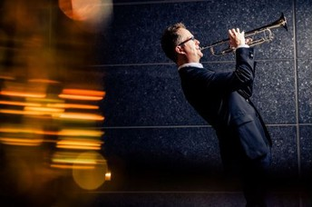 photo of lights and man in suit playing trumpet