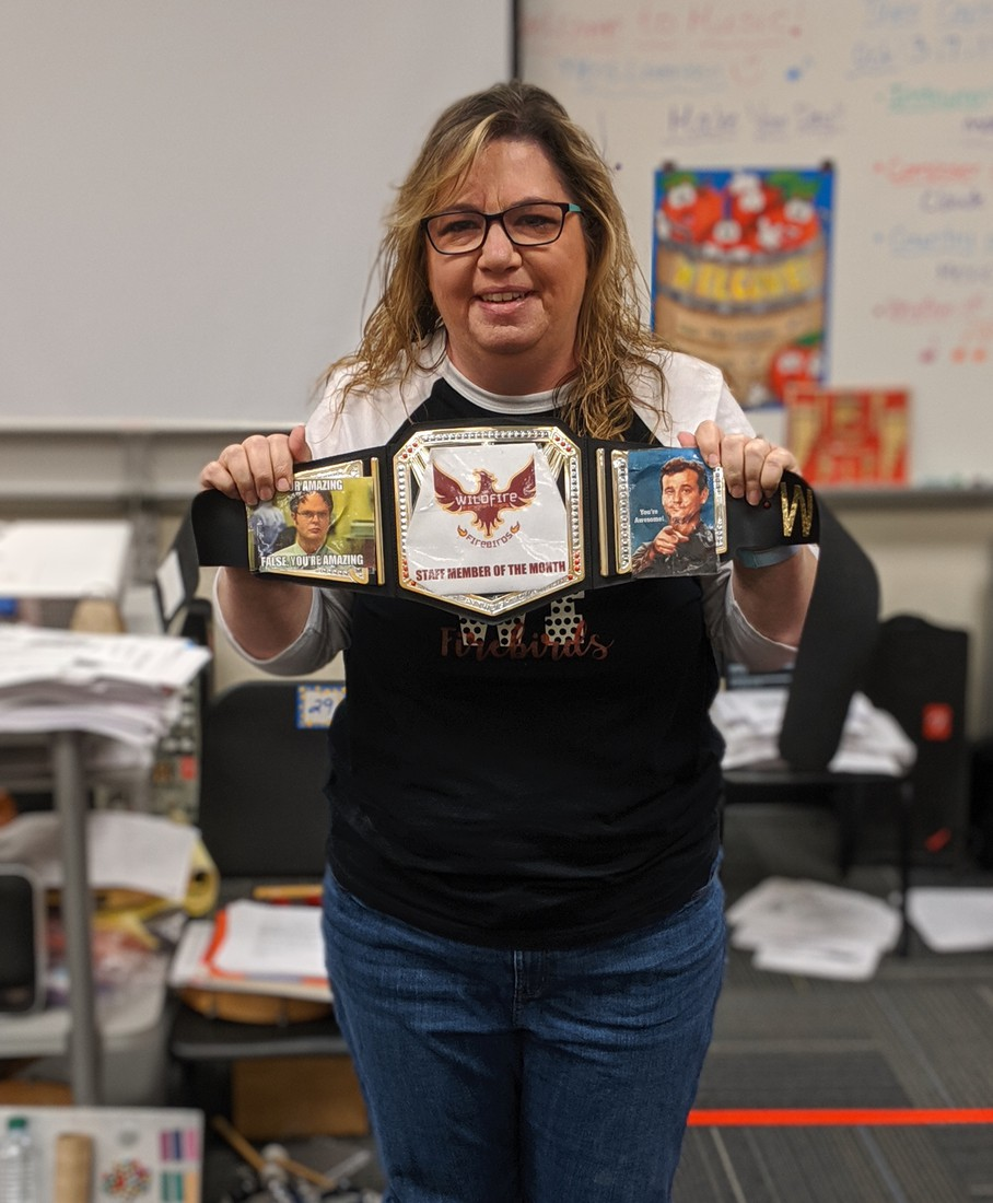Ms. Skinner holding up her staff member of the month belt