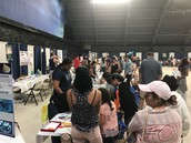 A throng of students crowd the booth